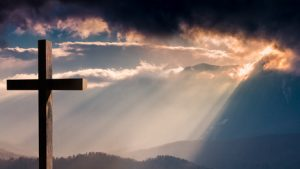 Jesus Christ cross. Easter, resurrection concept. Christian cross on a background with dramatic lighting, colorful mountain sunset, dark clouds and sky and sunbeams